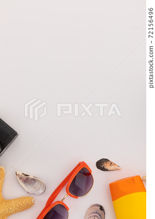 Camera, sunglasses, sun lotion and shells scattered on white background 72156496