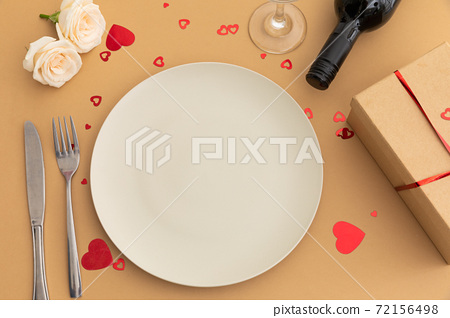 White plate, hearts, roses and wine on brown background 72156498