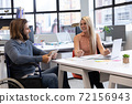 Caucasian businessman in wheelchair and businesswoman smiling in office 72156943