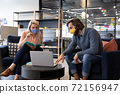 Caucasian businessman and businesswoman wearing face masks using laptop in office 72156947