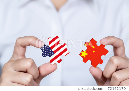 Hand holding USA and China jigsaw puzzle piece, Symbolic concept about trade war between USA and China. 72162170