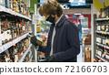 Handsome man choosing wine in the supermarket 72166703