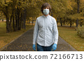 Man in mask walking in the park 72166713