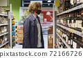 Handsome man choosing wine in the supermarket 72166726
