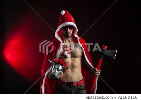 a man in a red Santa Claus Cape with an axe and a metal bull figurine symbol of the new year 2021 72168116