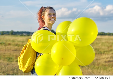 Portrait of happy teenager girl 15 years old with yellow balloons 72180451