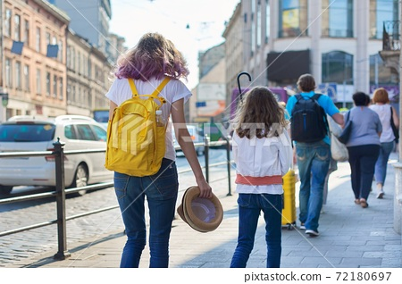 People walking on a city street, sidewalk, road with moving cars 72180697