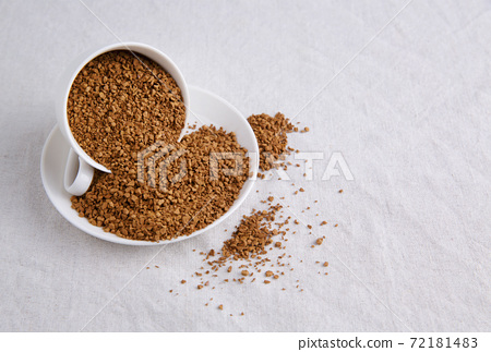 full mug of dry instant coffee as well as on saucer and on tablecloth 72181483