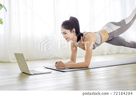 Young  woman in sportswear watching online video with fitness exercises on laptop 72184284