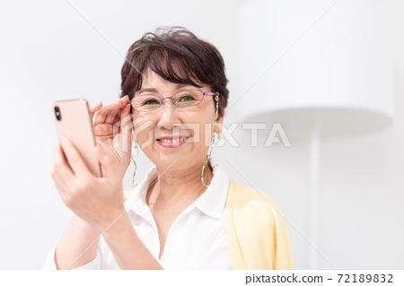 一個女人看著老花鏡的智能手機 72189832
