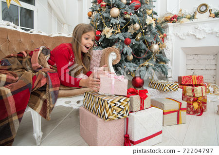 Happy new year. Winter. Opening her Christmas present.  72204797
