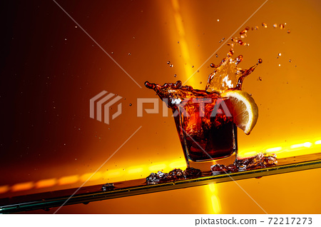 Slice of lemon falling into a glass of Cola. 72217273