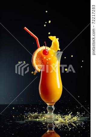 Orange juice with splashes on a black background. 72217283