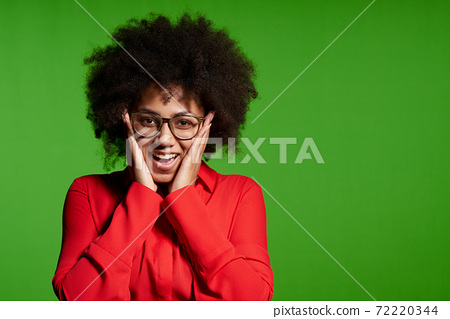 Happy excited young African-American girl looking at camera screaming with hands on cheeks 72220344