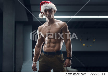 Fitness man in Santa Claus hat costume in gym 72228911