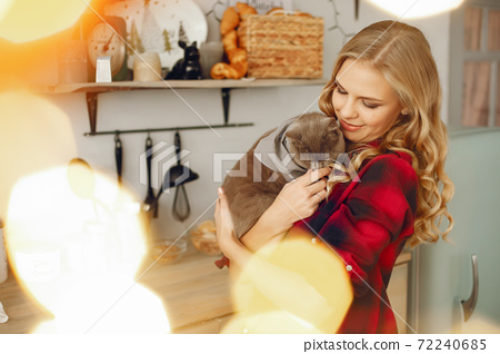 Beautiful girl playing with cat at home 72240685