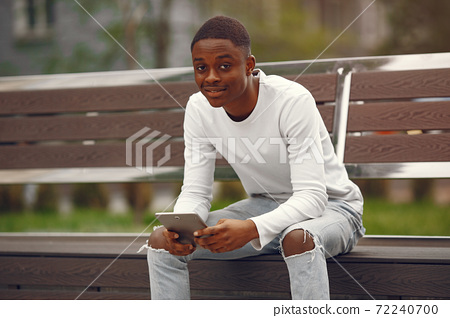 Black man in a white sweater in a summer city 72240700