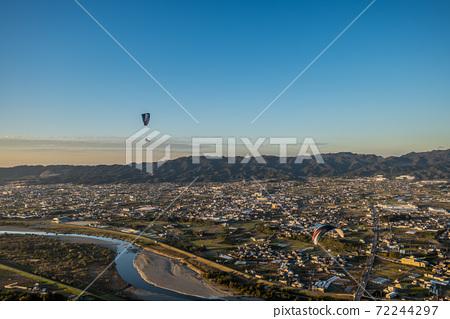 A paraglider flying over the Kinokawa River while bathing in the setting sun. Kinokawa City, Wakayama Prefecture 72244297