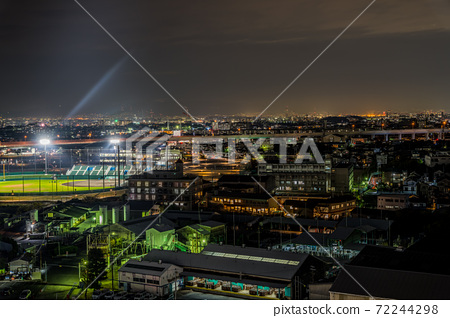A landscape with a baseball field in the ordinary night view of the cityscape. 72244298