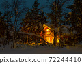 Night Snowy Forest and Illuminated Wooden Cottage 72244410