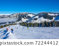 Lots of Skiers on a Wide and Gentle Ski Slope in Sunny Weather 72244412