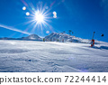 Snow-Covered Ski Slope and Ski Lift and Bright Sun 72244414