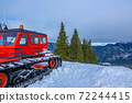 Red Snowcat and Cloudy Sky Over Winter Mountains 72244415