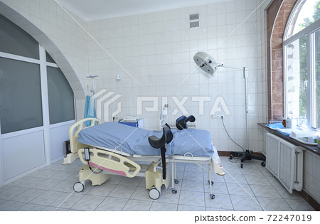 Delivery room of a maternity hospital, obstetric bed, lamp, medical equipment set 72247019