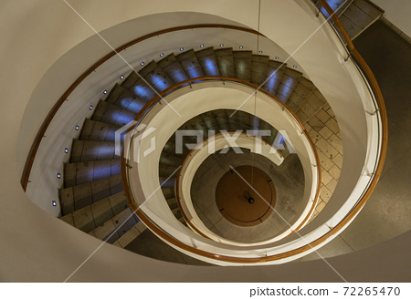 Spiral Staircase Leads Down Several Floors With Dramatic Lighting 72265470