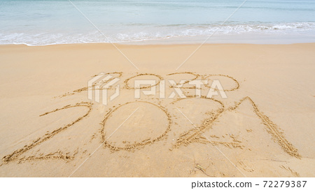 Photo of coming New Year 2021 Text and leaving year of 2020 of lettering Text on the beach with wave and white sea foam Numbers 2021 year on the seashore wave crashing on sandy shore 72279387