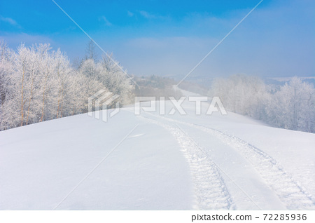trees in hoarfrost on a snow covered hill. fairy tale winter mountain landscape. foggy weather on a sunny day 72285936