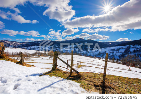 mountainous rural landscape on a sunny winter day. fields and trees on rolling hills covered in snow. fluffy clouds on the sky. beautiful carpathian landscape 72285945