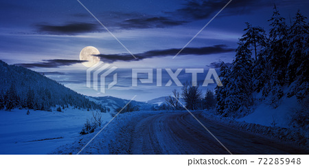 road through mountain landscape in winter at night. spruce forest covered in snow. dramatic sky with clouds glowing in full moon light 72285948