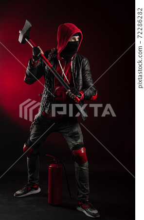 a man in a Balaclava and hoodie with an axe and a fire extinguisher the image of a Protestant 72286282