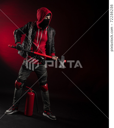 a man in a Balaclava and hoodie with an axe and a fire extinguisher the image of a Protestant 72286286