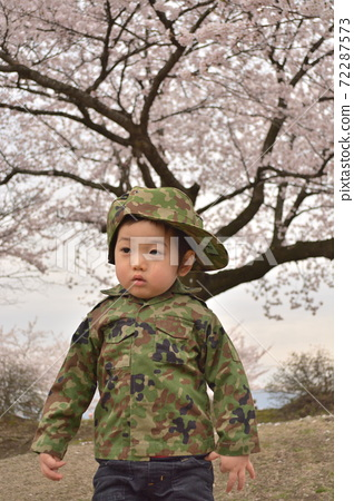 봄의 벚꽃을 배경으로 위장의 군복으로 살결 소년 72287573