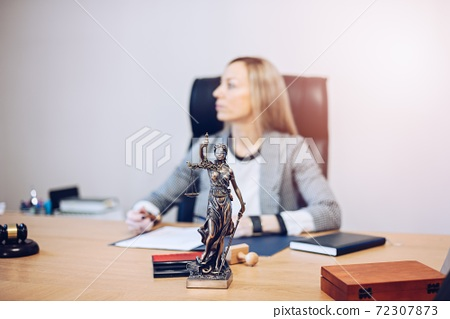 Female lawyer sitting at the wooden desk in the notary public office. 72307873