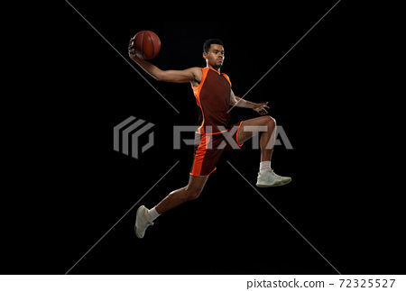 Young african basketball player training on black studio background. 72325527