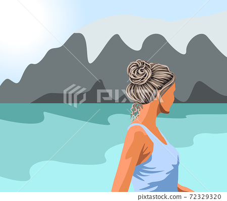 Gray haired woman in blue tank top looking at the lake and the mountains 72329320