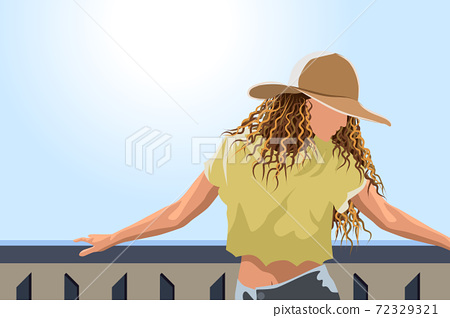 Woman in sun hat , yellow cropped t-shirt and jeans posing on the balcony 72329321