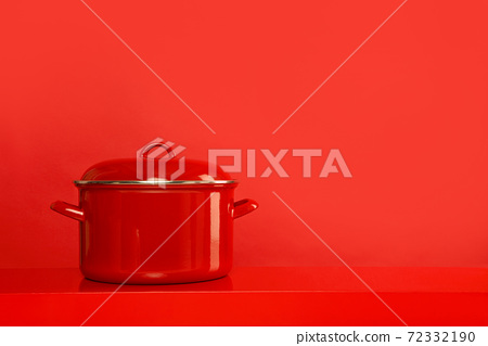 Red cooking pan on a red background with space for copy 72332190