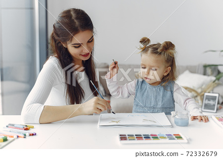 Tutor with litthe girl studying at home 72332679