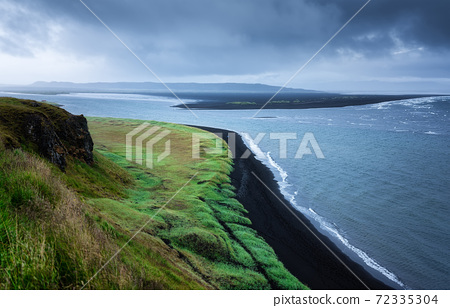 Seashore in Iceland. High rocks and grass at the day time near sea. 72335304