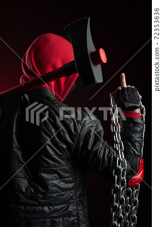 a man in a Balaclava and hoodies with an axe the image of a Protestant shows the middle finger 72353636