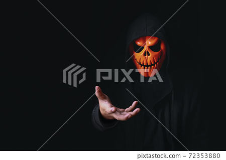 Horror devil costume with spooky pumpkin skull in black dressed for halloween carnival. Devil cosplay in ghost mask and raise hand with blank copy space for your advertising content. 72353880