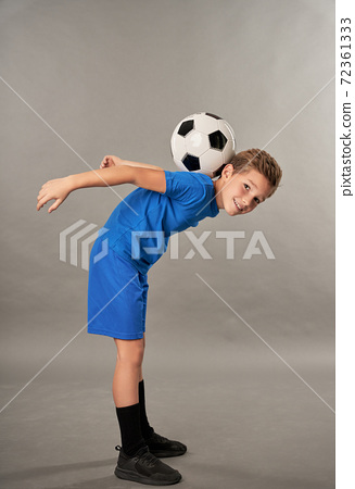 Cute boy with soccer ball on his back standing against gray background 72361333