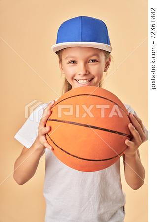 Adorable joyful girl in cap holding basketball ball 72361882