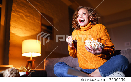 young  delighted cheerful woman with popcorn laughs and watches  movie on  TV   at home in evening  alone. 72363594