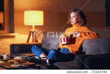 young  woman eats French fries and watches an exciting action-Packed movie on TV at home in evening  alone. 72363598
