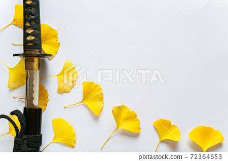 一把光禿的日本劍和多張黃色銀杏葉被放置在白皮書背景的左側。複製右上角的空間。 72364653